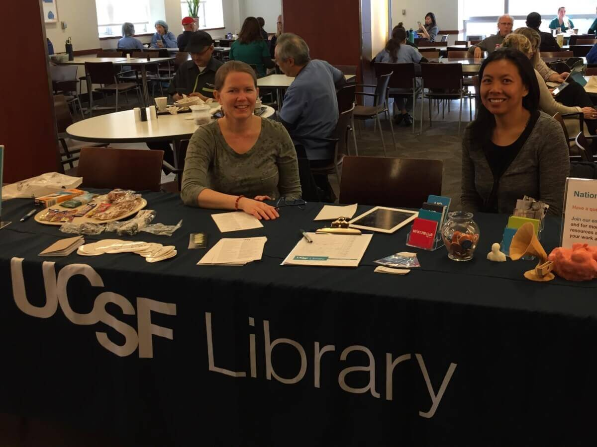 2 librarians at a table with handouts