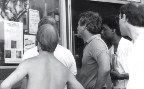"Black and white image of five men looking at a flyer with the title ""gay cancer."""
