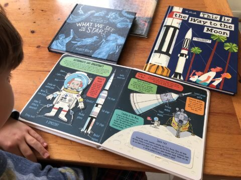 Child looking at books on space.